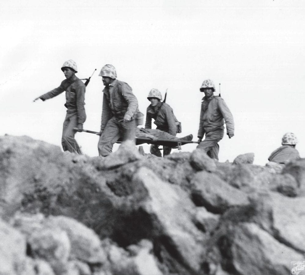 Stretcher bearers bring in a wounded Marine while under sniper fire near Motoyama Airfield No. 2. Corpsmen and stretcher bearers were among the favorite targets of the Japanese. MARINE CORPS HISTORICAL CENTER PHOTO