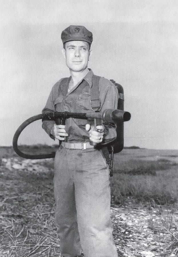 """Hershel """"Woody"""" Williams poses post-World War II with the type of flamethrower used in his Medal of Honor actions."""