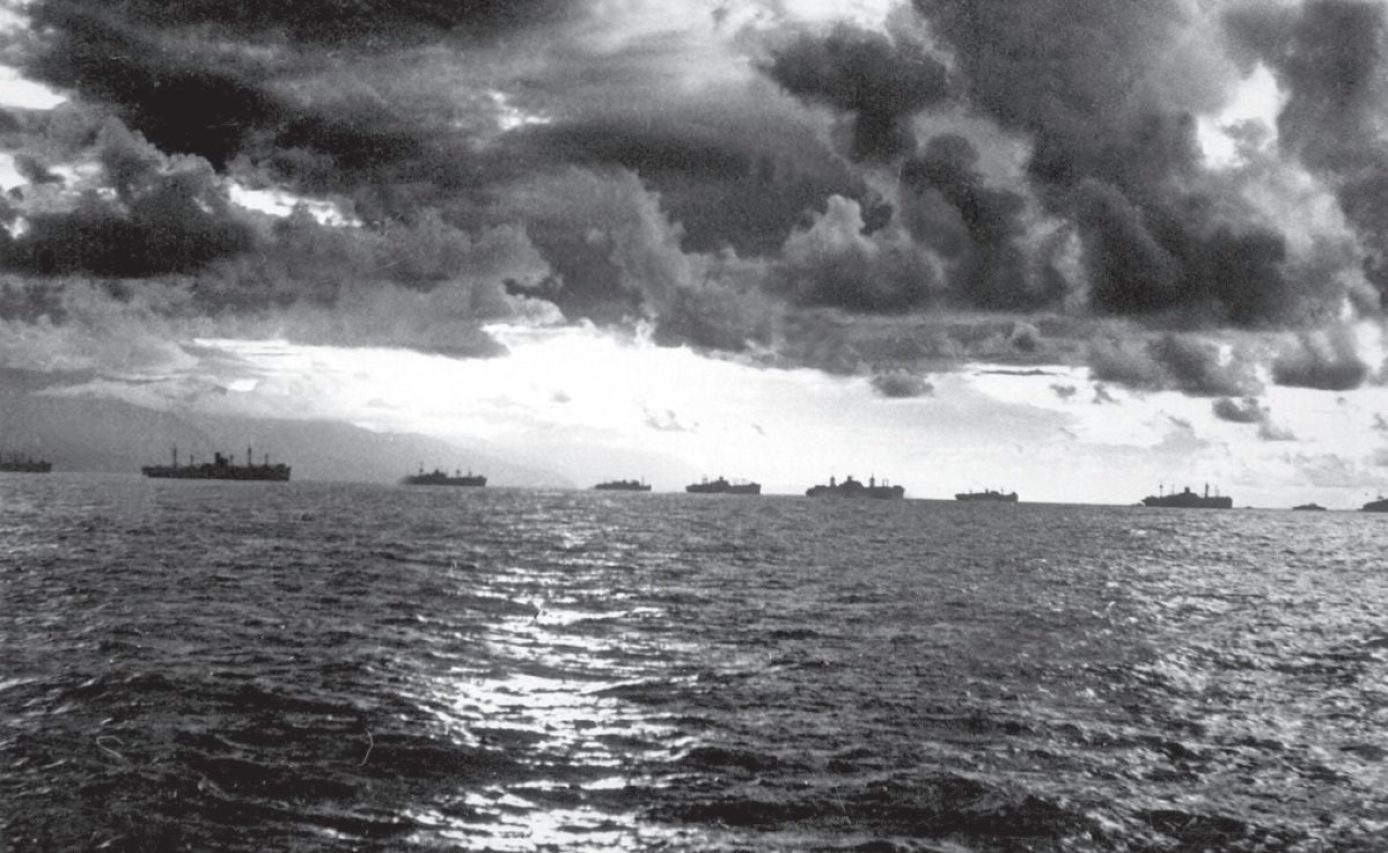 """A small part of the U.S. Navy fleet steams along the coast of Leyte island during the invasion of the Philippines in October 1944. While not as warlike and impressive as the """"murderers' row"""" of U.S. Navy aircraft carriers and other warships in the top photo, the ships shown here – transports and cargo ships, oilers, and support vessels – were what kept the fleet moving and fighting. National Archives Photo"""