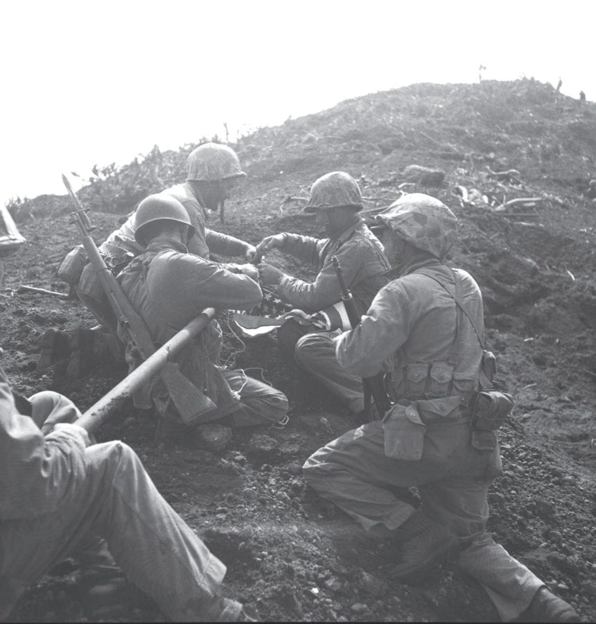 Preparing to raise the first American flag atop Mt. Suribachi. Lindberg is at top left, helping tie the flag to the piece of pipe that would serve as the flagpole. U.S. MARINE CORPS PHOTO BY LOU LOWERY