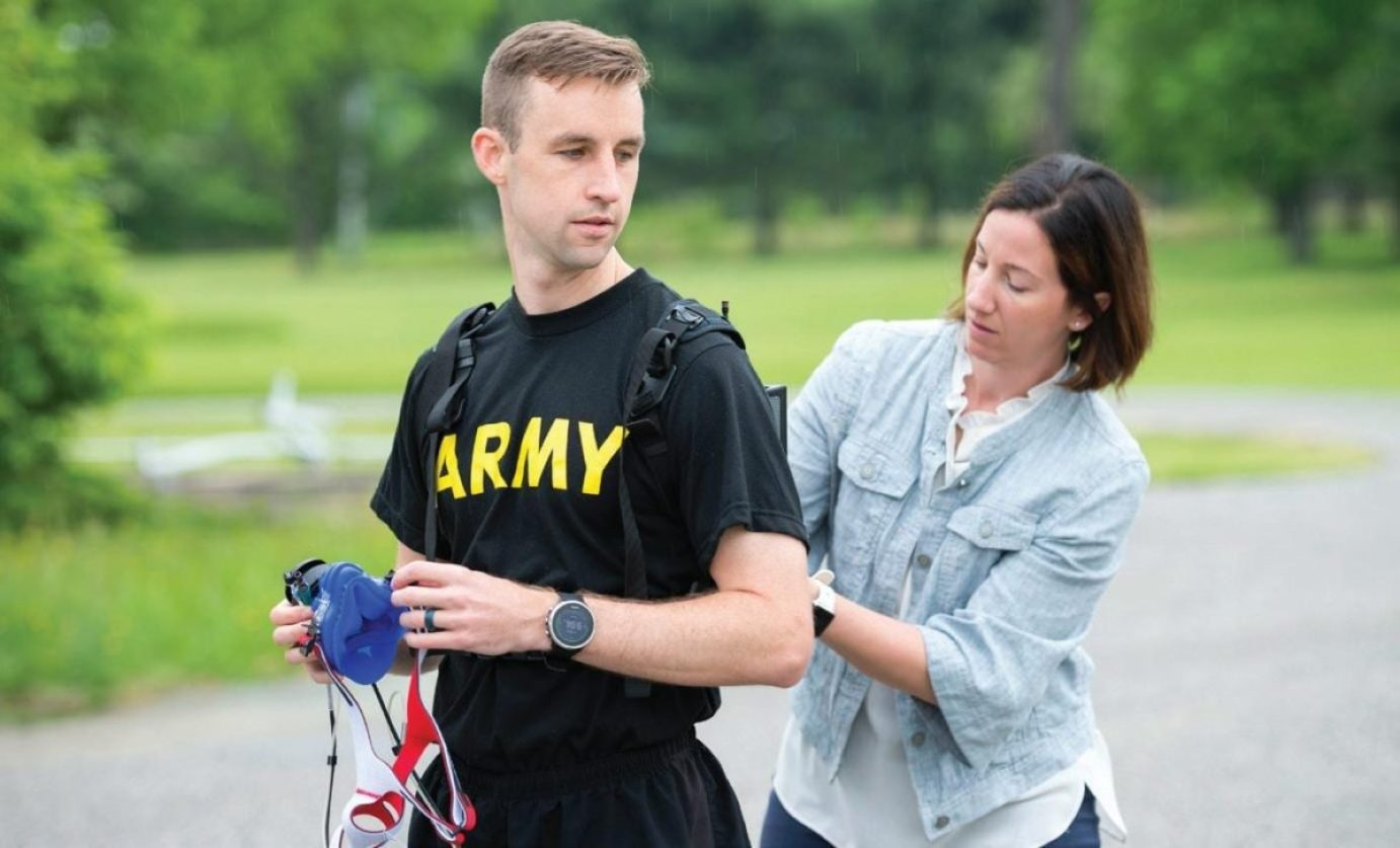 Megan Amadeo, Army Wellness Center project officer, Army Public Health Center, assists U.S. Army Capt. Zachary Schroeder, Headquarters and Headquarters Company commander, Army Public Health Center, with putting on the new K5 metabolic testing unit May 9, 2019, as part of his training to compete in the Army Ten Miler in October 2019. The K5 portable VO 2 unit, which is available at certain Army Wellness Center locations, allows soldiers and athletes to measure how well their muscles use oxygen, and can be used to optimize performance and train for events.