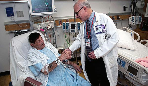 In this 2015 photo, World War II Marine veteran Stanley Frable, who took part in the COURAGE trial, meets with Dr. Steven Sedlis, then the chief of the cardiology section at the Manhattan VA Medical Center. The VA is working to implement findings from the COURAGE trial.