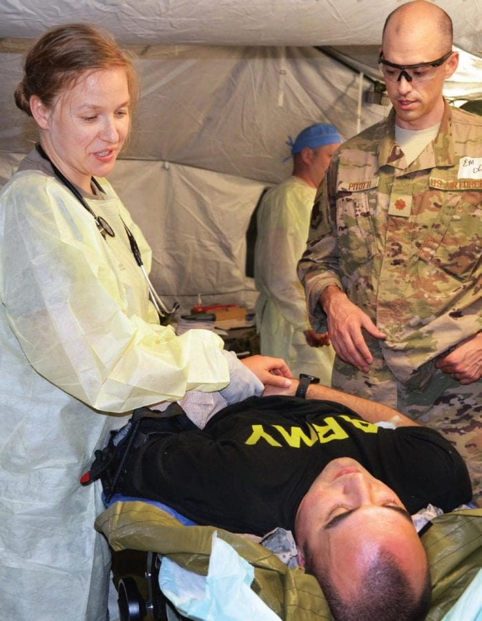 Carl R. Darnall Army Medical Center (CRDAMC) emergency medicine (EM) resident Capt. Katey Bettencourt examines a simulated casualty while Air Force Maj. Chris Pitotti, EM residency program associate director, University of Nevada, observes during CRDAMC's Joint Emergency Medicine Exercise held May 28-31, 2019. The exercise tested the Tactical Combat Casualty Care readiness of Army, Air Force, and Navy EM residents in a simulated real-world, joint operational medicine environment. The transition to DHA will facilitate the implementation throughout the Military Health System of best practices in military medical care from all the services.