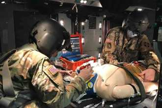 Capt. Erickson Shuler and Capt. Rebecca Rosales asses and treat a patient (mannequin) while on a Blackhawk during the U.S. Army School of Aviation Medicine Flight Nurse course, Fort Rucker, Alabama, May 29th 2020. (Courtesy Photo)