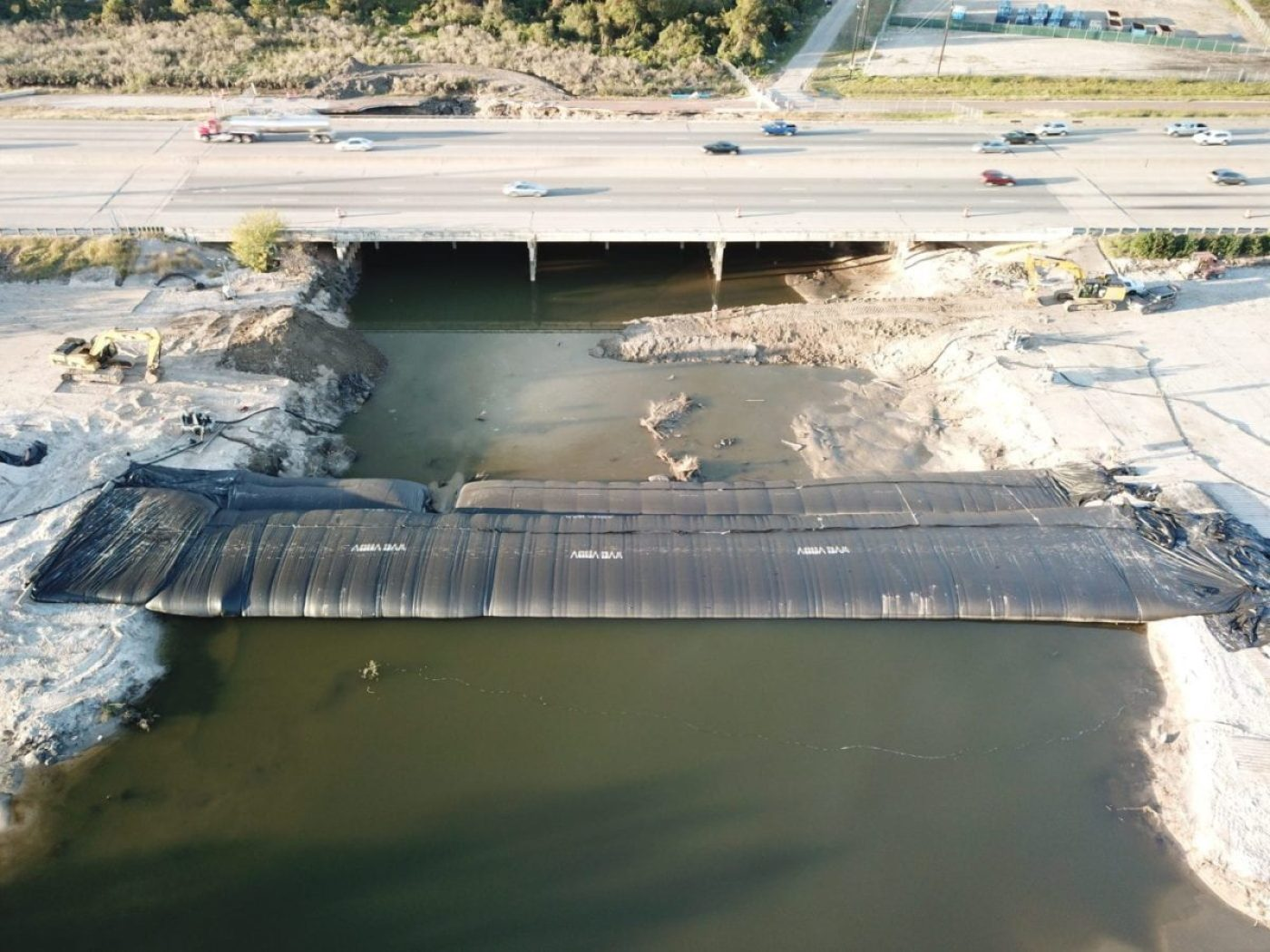 The Isolation of these bridge piers, for post-Hurricane Harvey inspection and scour repair, was achieved using a combination of 300ft long by 16ft tall sections of AquaDam supported by 8ft AquaDam sections. (AquaDam image)