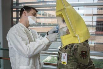 Army 1st Lt. Liston Barber, Public Health Command – Central environmental science officer, administers an N95 respirator fit test for Air Force 1st Lt. Jennifer Rossi, registered nurse, at Brooke Army Medical Center, Fort Sam Houston, Texas, April 17, 2020. The N95 respirator is a respiratory protective device designed to form a seal around the nose and mouth and provides very efficient filtration of airborne particles. (U.S. Army photo by Jason W. Edwards)