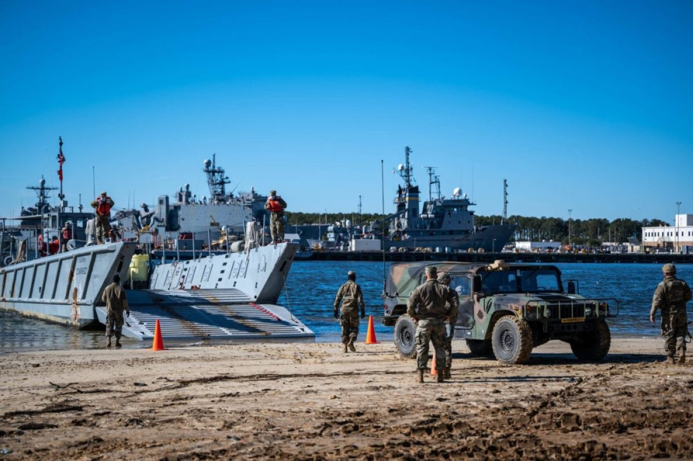 U.S. Army Soldiers from the 10th Transportation Battalion (Terminal) assigned to Joint Base Langley-Eustis prepare to load a Humvee onto a landing craft mechanized (LCM) during a Logistics Over-the-Shore (LOTS) training at Joint Expeditionary Base-Little Creek, Virginia, Feb. 4, 2021. The battalion deploys worldwide to provide watercraft and maintenance assets to conduct Combined, Joint and or Service LOTS, Intra-theater lift and riverine operations in support of the operational commander. (U.S. Air Force photo by Senior Airman Anthony Nin Leclerec)