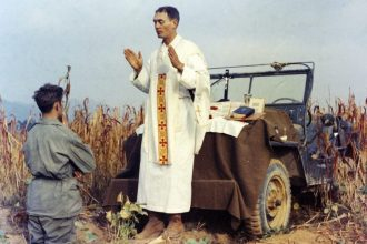 Father Emil Kapaun celebrates Mass using the hood of his jeep as an altar, as his assistant, Patrick J. Schuler, kneels in prayer in Korea on Oct. 7, 1950, less than a month before Kapaun was taken prisoner. Kapaun died in a prisoner of war camp on May 23, 1951. (Col. Raymond A. Skeehan)