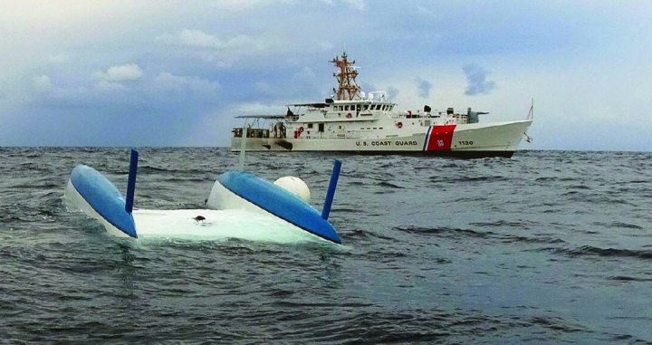 The 30-foot sailing vessel Divided Soul floats capsized near the Coast Guard Fast Response Cutter Robert Ward Feb. 10, 2019, 10 miles west of Torrey Pines, California. The crew of the Robert Ward rescued three people who had been aboard the sailing vessel when it capsized. (U.S. Coast Guard photo)