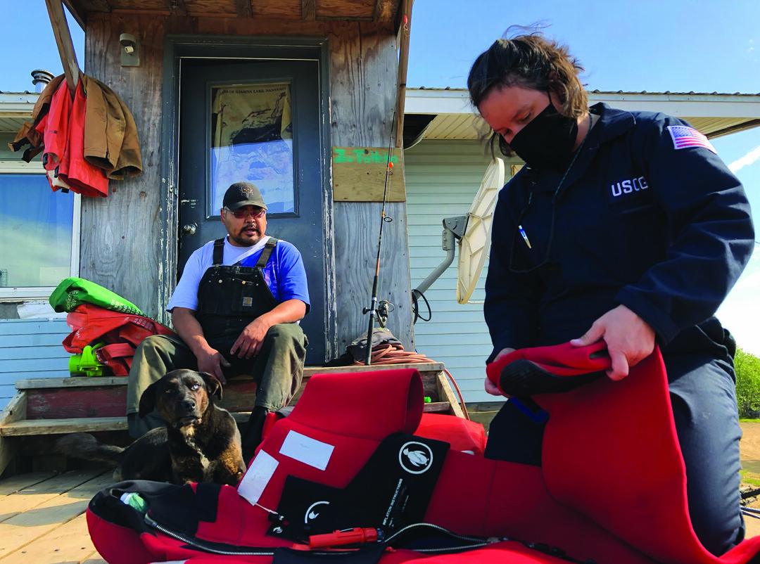 Coast Guard Petty Officer 2nd Class Para Upchurch (right), a marine inspector with Sector Anchorage, inspects a survival suit as part of a commercial fishing vessel safety exam for the Miss Avena in Levelock, Alaska, June 16, 2020. Coast Guard inspectors with Sector Anchorage's Marine Safety Task Force conducted inspections throughout the Bristol Bay region June 9-26 to prepare the salmon fishing fleet for a safe season. (U.S. Coast Guard photo by Petty Officer 1st Class Nate Littlejohn)
