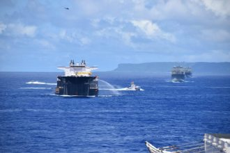 While steaming in a formation near Guam, USNS Montford Point employs their hose, a pre-planned response, which it might use during convoy operations. Pictured from left are: a Coastal Riverine Group 1's mark VI boat, USNS Montford Point (T-ESD 1), U.S. Coast Guard Cutter Myrtle Hazard (WPC-1139), USNS Red Cloud (T-AKR 313), USNS Watkins (T-AKR 315), and in the air, an MH-60R from Helicopter Sea Combat Squadron 25. (Photo by Lt. j.g. Nathaniel Ventura)