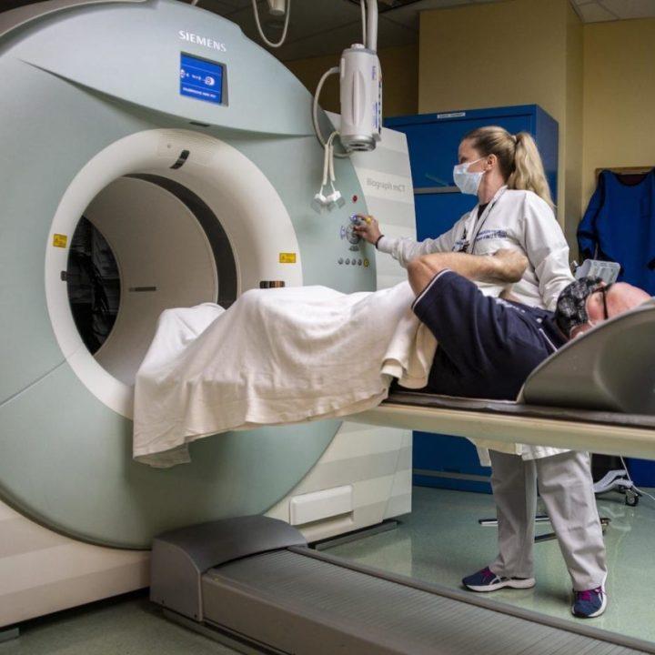 technologist, prepares a patient for a positron emission tomography (PET) scan