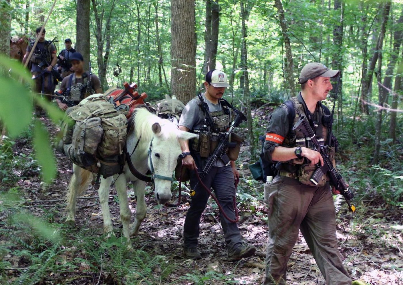 Special Forces candidates assigned to the U.S. Army John F. Kennedy Special Warfare Center and School lead mules down a path as part of a long-distance movement during the final phase of field training known as Robin Sage in central North Carolina, June 7, 2020. Robin Sage is the culmination exercise for Soldiers in the Special Forces Qualification Course and has been the litmus test for Soldiers striving to earn the Green Beret for more than 50 years. Soldiers are evaluated on various skills required to not only successfully operate on a Special Forces Operational Detatchment Alpha, but on the battlefields of today and tomorrow. (U.S. Army photo illustration by K. Kassens)