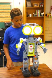 student-poses-with-robot