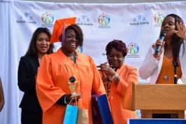 first DeKalb GED program graduate smiles in regalia