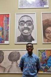 student poses beneath self-portrait
