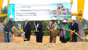 district officials in hard hats and shovels