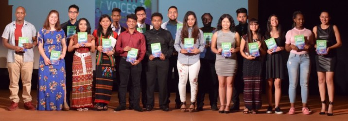 student authors hold copy of book