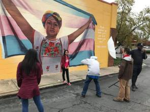 students take picture in front of mural