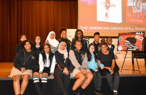 group of students pose on stage with Nic Stone