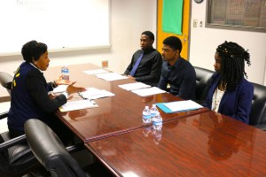 Leola Hatcher speaks with 3 students at table