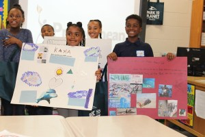 students hold project posters