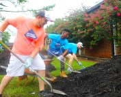 three men shovel mulch