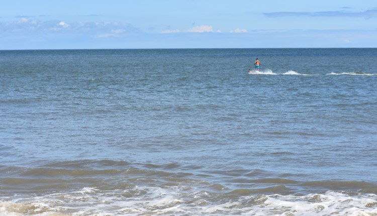 Guy on a motorized  board off the beach in Cape Henlopen State Park  jet surf