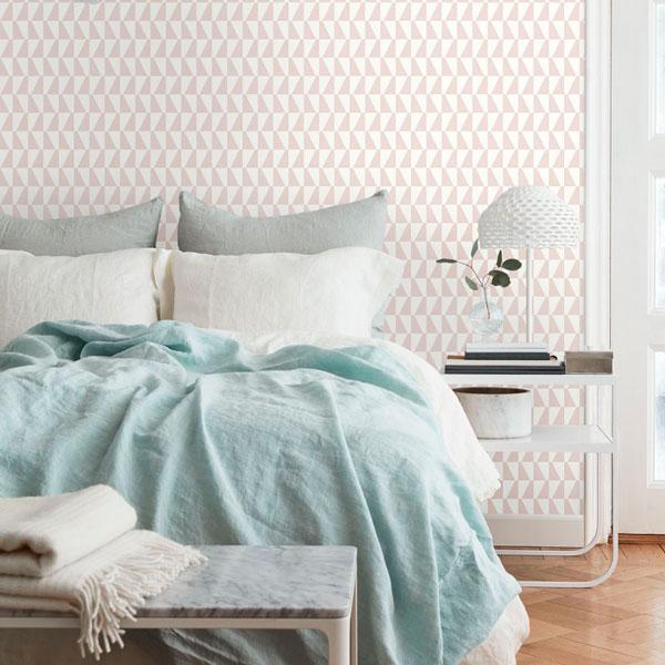 Papel pintado Trapez II en color rosa de la colección Scandinavian Designers II de Borastapeter en la pared de un dormitorio