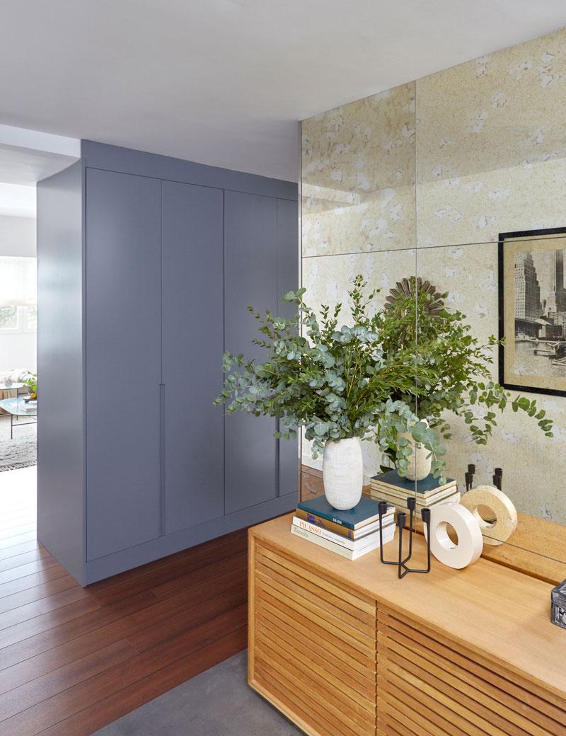 recibidor con pared de espejo antiguo y armario lacado en azul