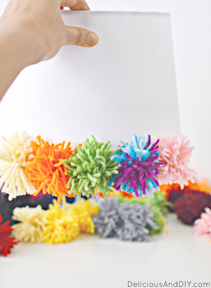 DIY Pom Pom Lamp Shade Makeover to add a pop of color and transform a drab lamp into a fun home decor item| DIY Lamp Makeover Ideas| DIY Ikea Lamp Makeover Ideas| Lampshade Ideas| Craft Project Ideas| Yarn Ideas| DIY Yarn Projects to update an old lampshade| Pom Pom Lamp Update Idea