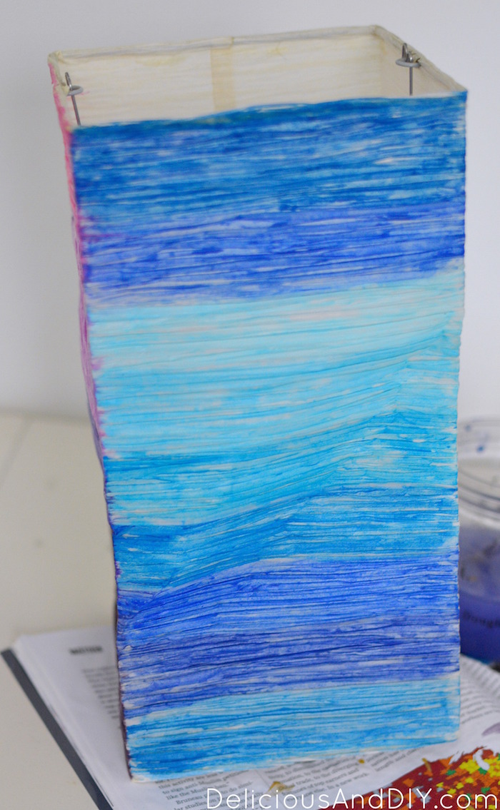 ikea lampshade being painted with blue watercolor paints