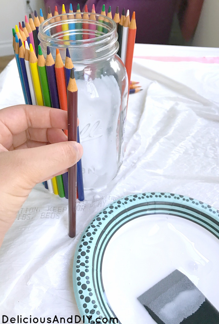 Applying glue and attaching pencil to mason jar