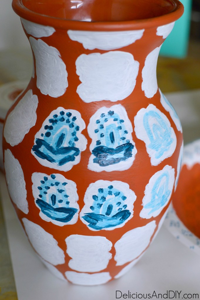 Painting with a dark blue paint color on top of the light blue pattern
