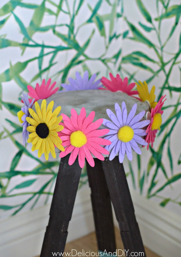 Colorful Felt flowers attached to the sides of a concrete plant stand