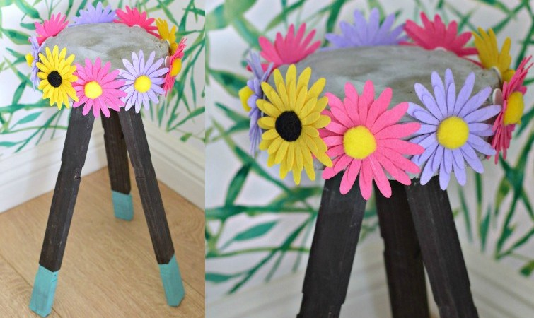 DIY Concrete Plants Stand made with wooden legs which it have half dipped in turquoise paint with colorful flowers attached on all sides of the concrete top