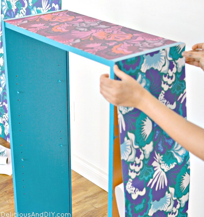 Blue floral Peel and Stick Wallpaper being applied to the outside of the bookshelf