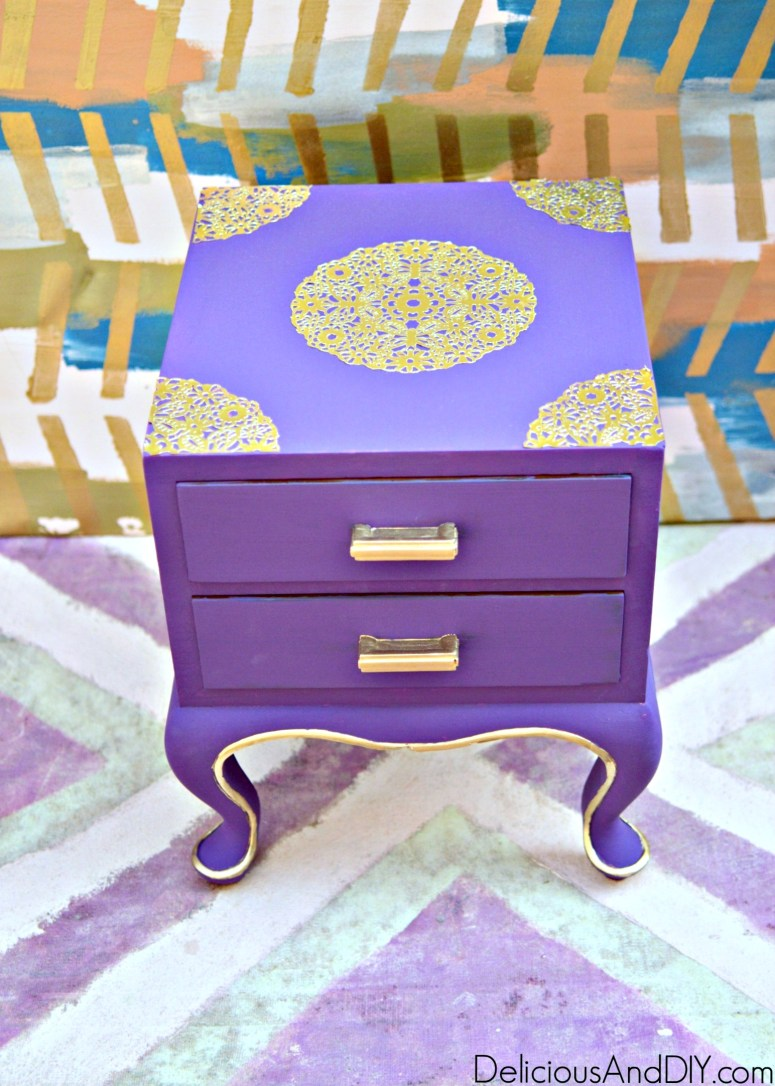 a thrifted nightstand painted purple and decouapaged with gold doilies