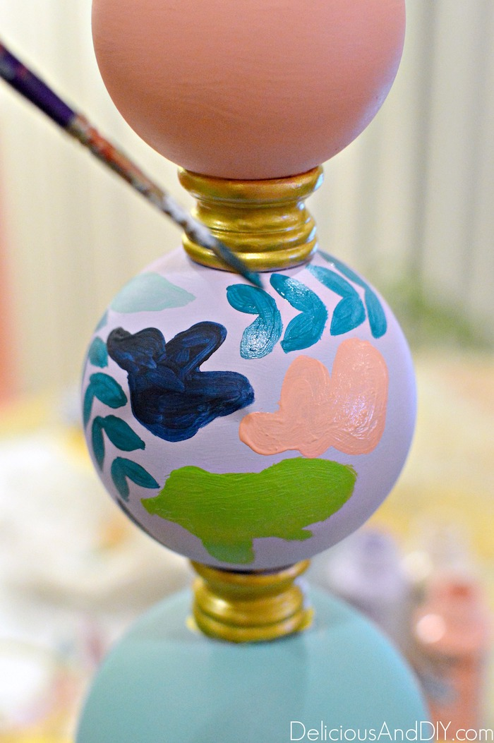 painting a floral pattern onto a thrifted lamp base