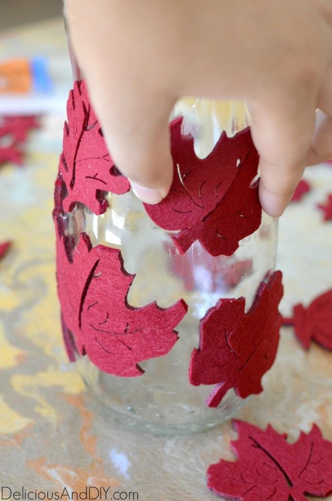 attaching felt fall leaves onto glass bottle