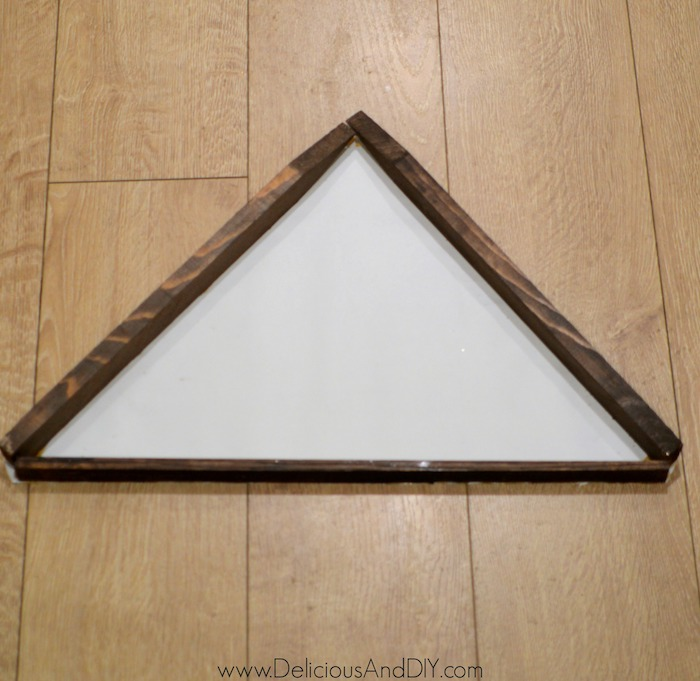 gluing the wooden stakes in a triangle shape onto paper