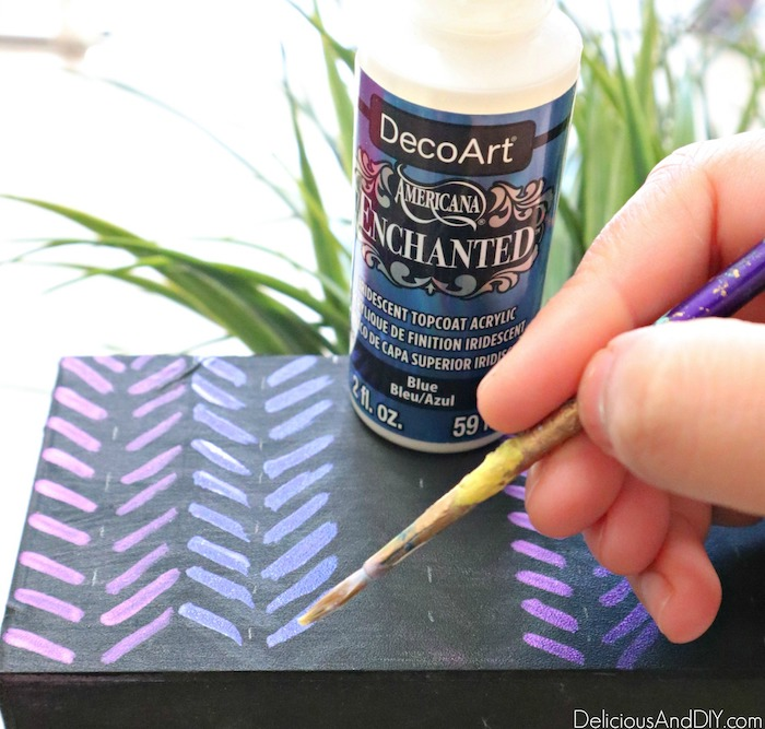 painting blue paint in an aztec pattern