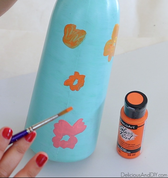 orange flowers being painted onto the dollar store vase
