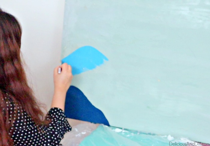 painting light blue layer of the paint onto the wall art