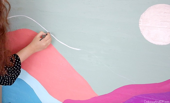 painting white line to create a mountain silhouette