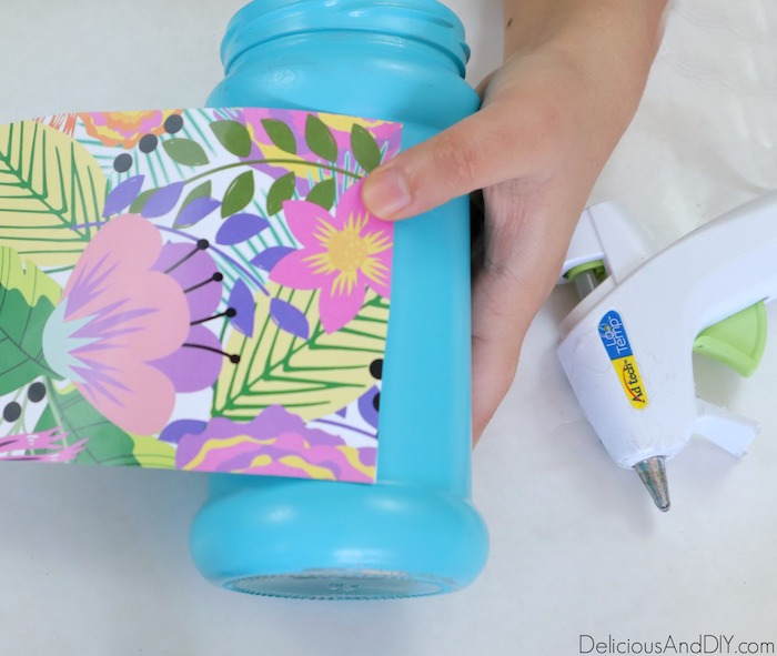 floral pattern paper being glued onto the bottle