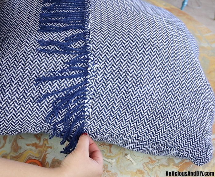 gluing the fringe onto the throw pillow