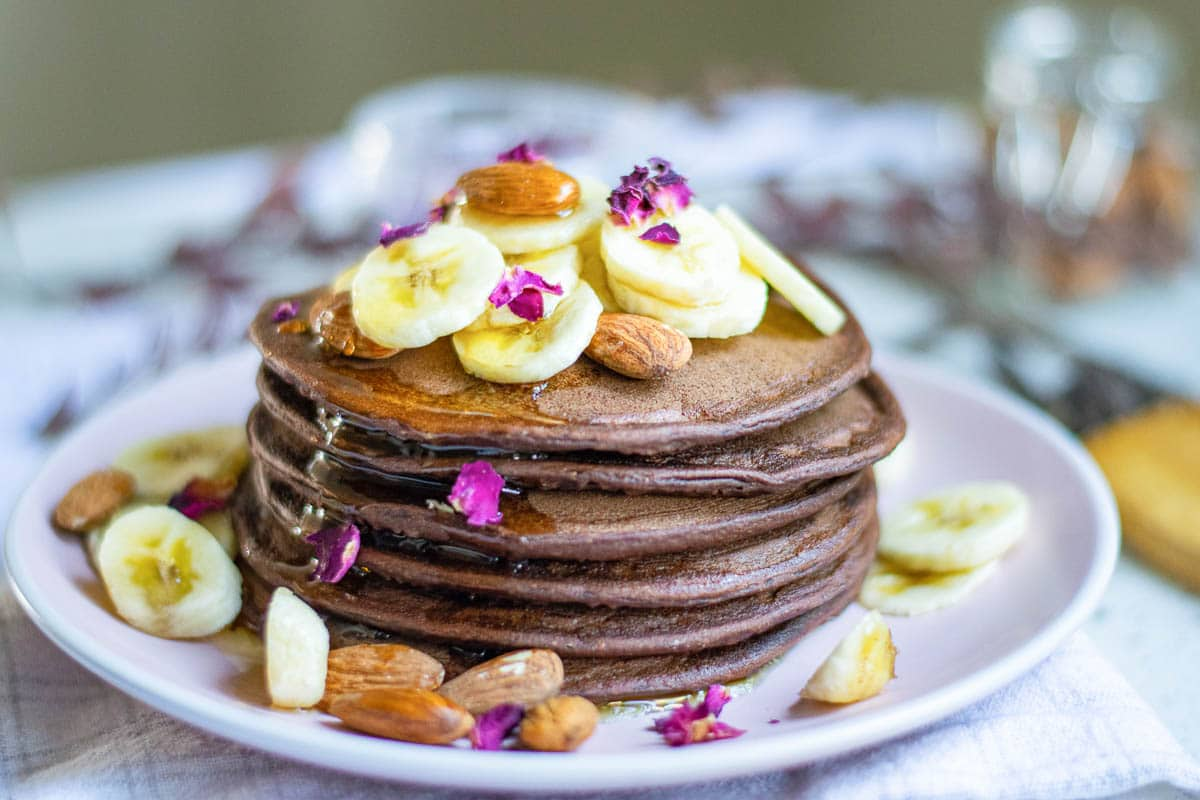 chocolate banana pancakes on a plate topped with almonds, bananas, and pink petals