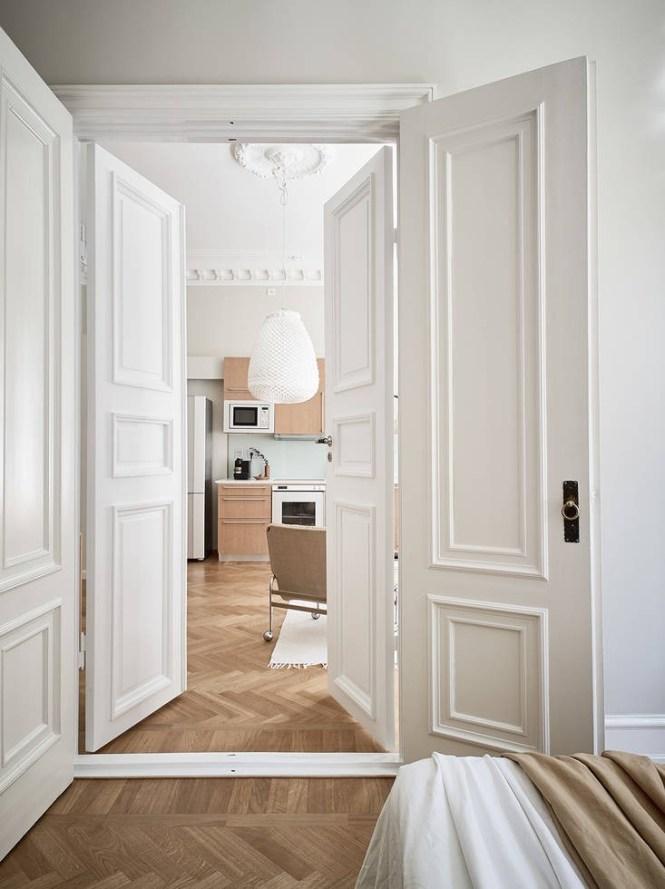 suelo de madera espigada puertas dobles interior Molduras en el techo grandes ventanales distribución diáfana detalles arquitectonicos chimenea sueca