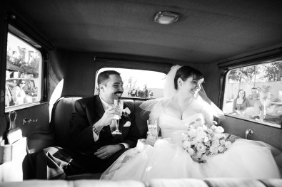 bride and groom smiling at guests inside the limo